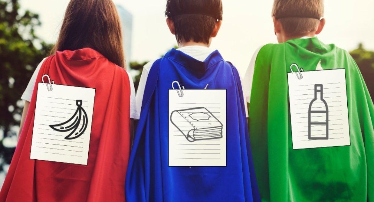 Trójka dzieci tyłem w pelerynach jak superbohater, na pelerynach etykiety śmieci